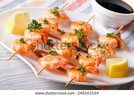 grilled shrimp on skewers close-up on a plate and sauce. horizontal  - stock photo