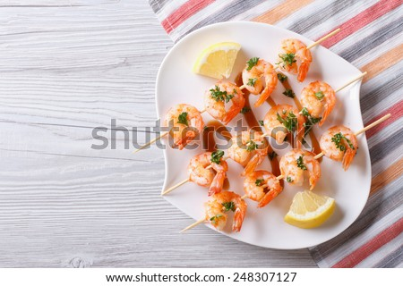 Grilled shrimp on skewers with lemon on a plate. horizontal view from above