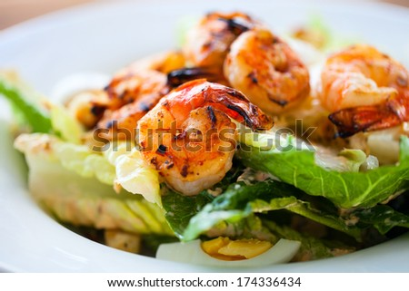 Grilled shrimps and fresh green salad served for lunch - stock photo