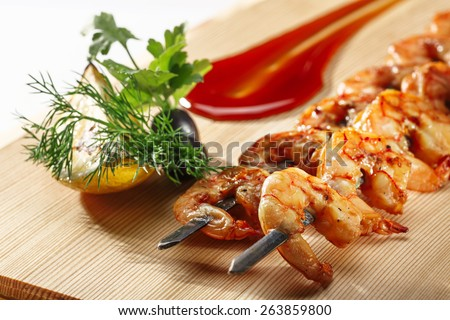 Grilled shrimps on a elegant skewers decorated with greens and sauce. Prawn kebab. Healthy seafood dinner. - stock photo