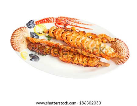 Grilled shrimps on a wooden stick lying on a dish.Isolated. - stock photo