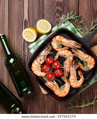Grilled shrimps on frying pan and beer on wooden table. Top view - stock photo