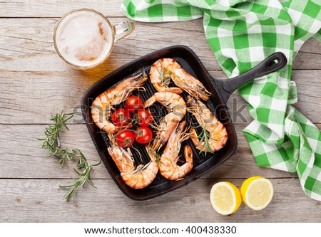 Grilled shrimps on frying pan and beer. Top view - stock photo