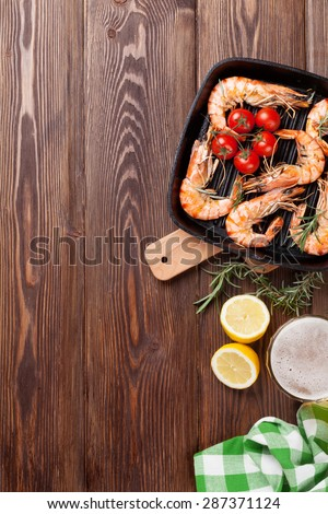 Grilled shrimps on frying pan and beer. Top view with copy space - stock photo