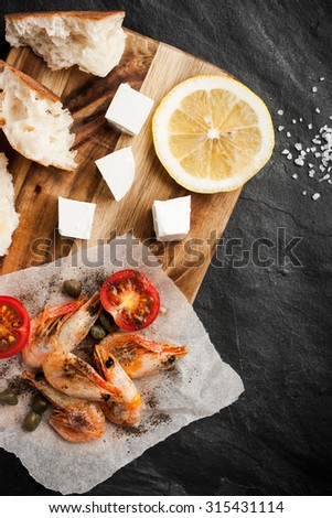 Grilled  shrimps  on the peace of paper with different snack on the black stone table vertical