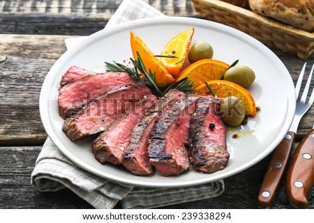 Grilled sirloin steak with orange - stock photo