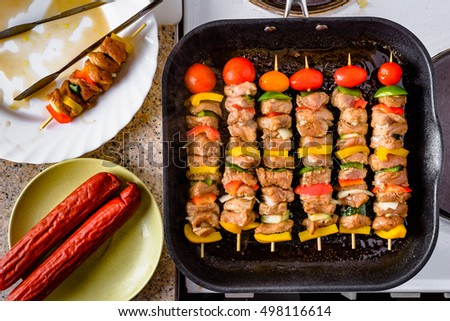 Grilled skewers on wooden sticks, pork meat and vegetables on grill.