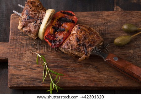 Grilled skewers with spices and vegetables on wooden background - stock photo