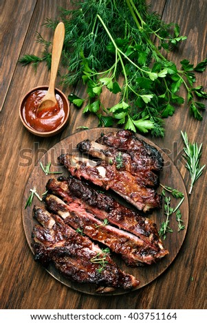 Grilled sliced barbecue pork ribs on wooden background, top view - stock photo