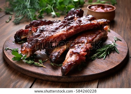 Grilled sliced barbecue pork ribs on wooden board, shallow depth of field