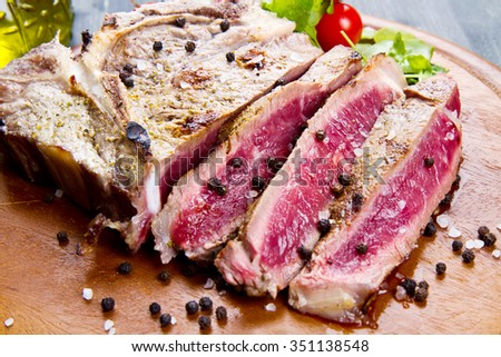 grilled sliced meat fillet on wooden background - stock photo