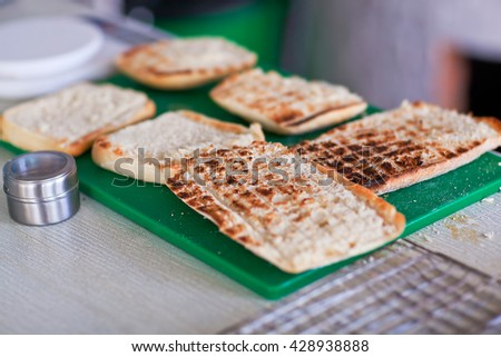 Grilled slices of bread for panini on the green stand. - stock photo