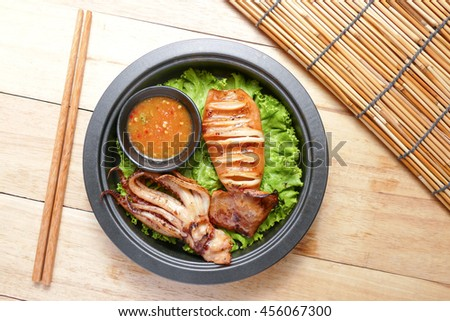 Grilled squid and vegetable with spicy seafood sauce on frying pan over wood table - stock photo