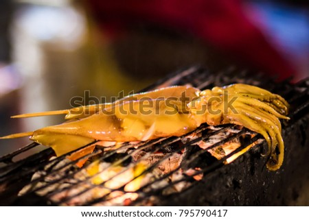 Grilled squid in Thailand night market. Blurred picture. Grain photo. Noise Background. Blurred Background.