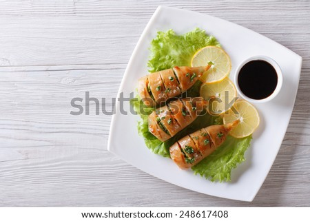 Grilled squid on a plate with lemon and sauce. horizontal view from above  - stock photo