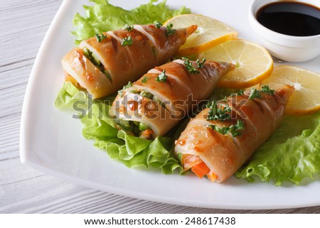 Grilled squid stuffed with vegetables with lemon and sauce closeup. horizontal  - stock photo