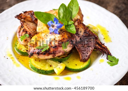 Grilled squid with lemon and zucchini on wooden background