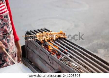 Grilled squids on stick, Thai street food. - stock photo