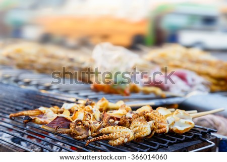 Grilled squids on stick, Thai street food with blur background of other food car and bus - stock photo