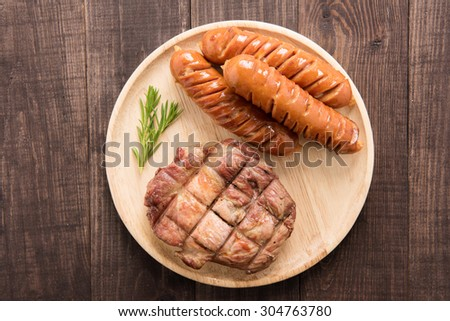 Grilled steak and sausage on a wooden background. - stock photo