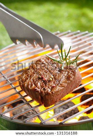 Grilled steak and tong on the grilling pan - stock photo