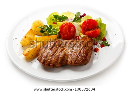 Grilled steak, baked potatoes and vegetable salad - stock photo
