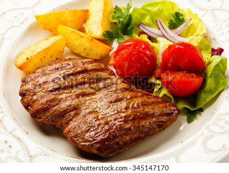 Grilled steak, baked potatoes and vegetable salad