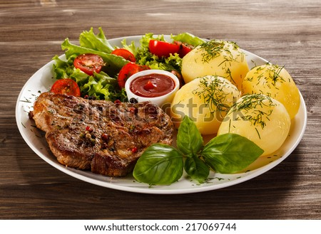 Grilled steak, boiled potatoes and vegetable salad