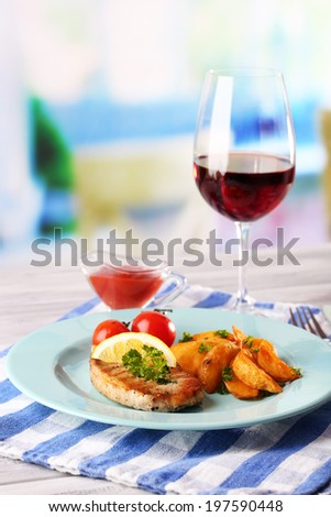 Grilled steak, grilled vegetables and fried potato pieces on table, on bright background