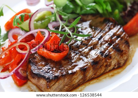 Grilled steak meat with salad from baked pepper - stock photo