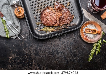 Grilled steak on grill pan with rosemary and spices , dark rustic metal background, top view, place for text, border - stock photo