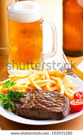 grilled steak with french fries and beer