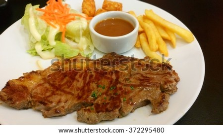 Grilled steak with french fries and vegetables - stock photo