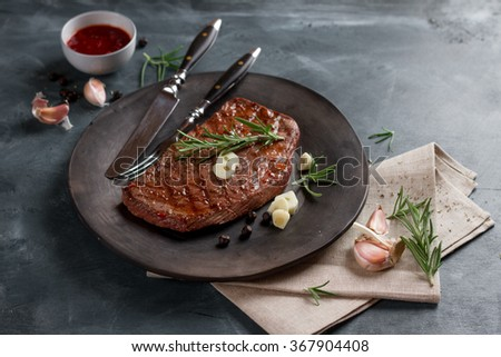 Grilled steak with garlic and rosemary on plate, selective focus - stock photo