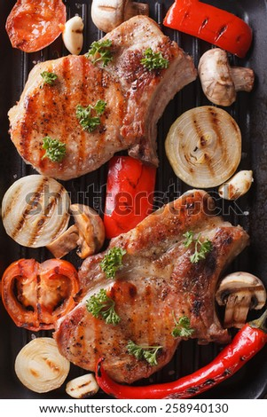 Grilled steak with mushrooms and vegetables on grill macro. vertical view from above