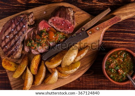 Grilled steak with potato wedges, salsa and spices on dark wooden background. - stock photo