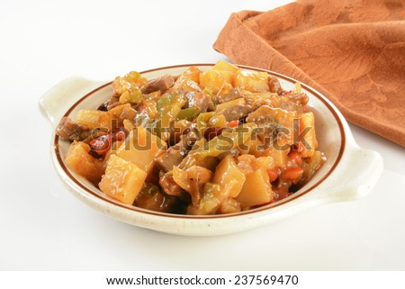 Grilled steak with potatoes, peppers and gravy on a white counter - stock photo