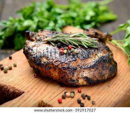 grilled steak with rosemary on a wooden background