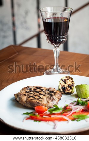 Grilled steak with vegetables and red wine glass
