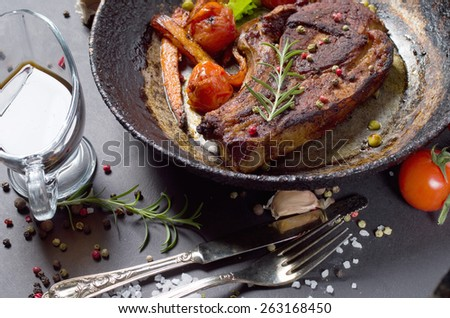 grilled steak with vegetables on a frying pan - stock photo