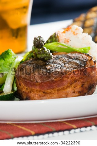 Grilled steak wrapped in bacon, with grilled vegetables, mashed potatoes, garlic toast, and lemon iced tea. - stock photo