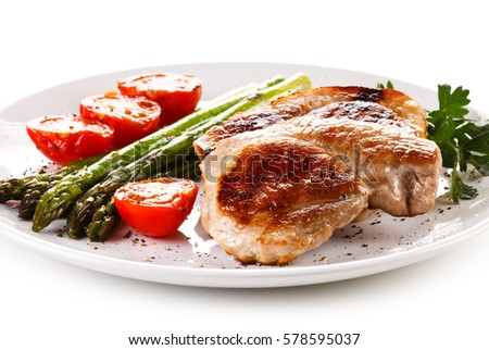 Grilled steaks and asparagus on white background