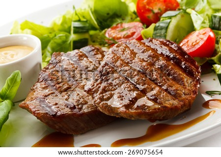 Grilled steaks and vegetable salad - stock photo