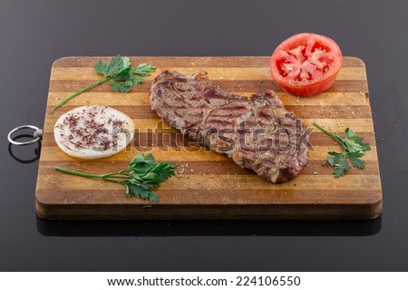 Grilled Steaks and Vegetables On a Wood Plate - stock photo