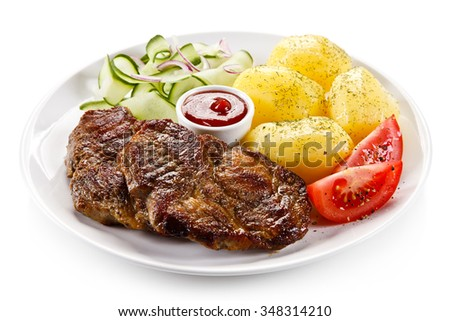 Grilled steaks, boiled potatoes and vegetable salad  - stock photo