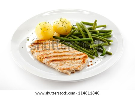 Grilled steaks, boiled potatoes and vegetables - stock photo