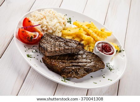 Grilled steaks, French fries and vegetable salad