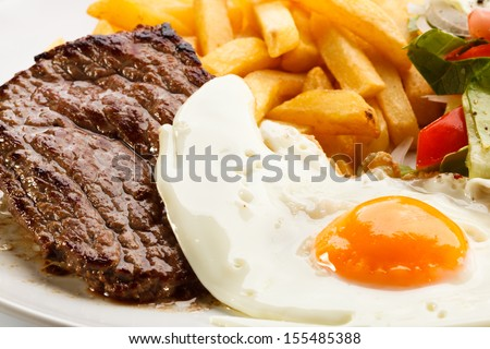 Grilled steaks, French fries, fried egg and vegetables - stock photo