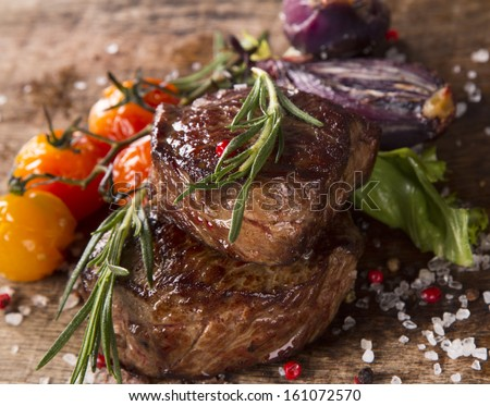 Grilled steaks on wood - stock photo