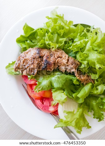 Grilled steaks or Fillet of Pork Steak with vegetables salad on white dish